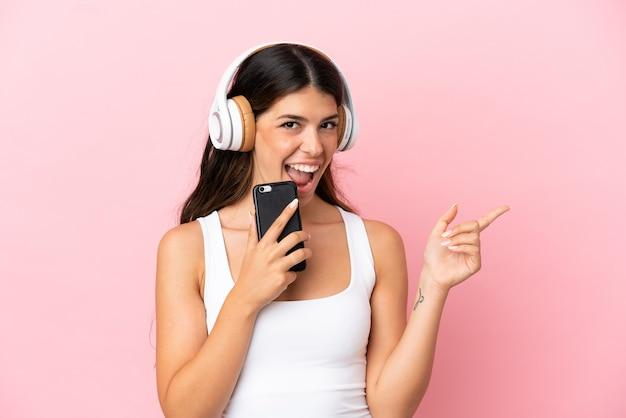 Giovane donna caucasica isolata su sfondo rosa ascoltando musica con un cellulare e cantando
