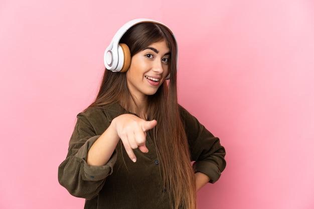Giovane donna caucasica isolata su sfondo rosa ascoltando musica