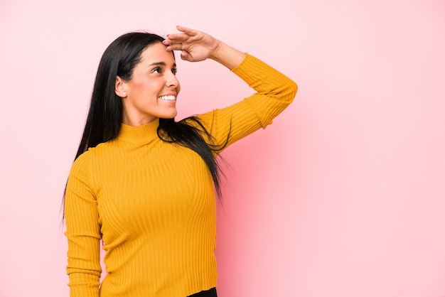Giovane donna caucasica isolata su sfondo rosa guardando lontano tenendo la mano sulla fronte.