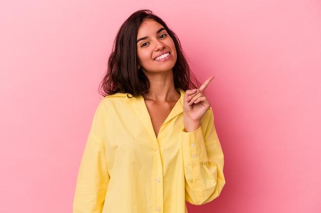 Giovane donna caucasica isolata su sfondo rosa che mostra il numero uno con il dito.