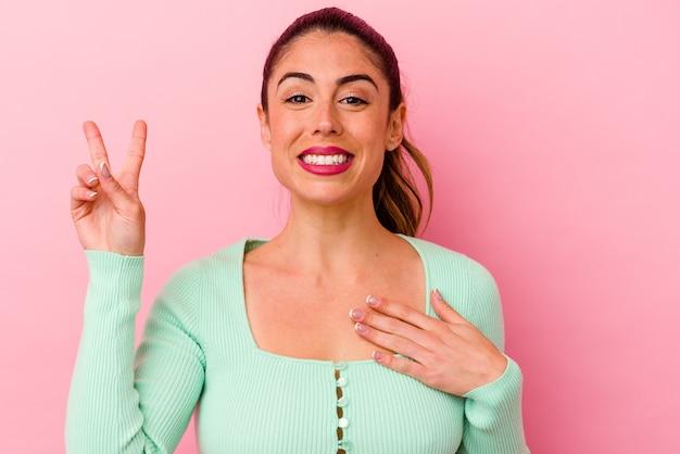 Giovane donna caucasica isolata su sfondo rosa che soffre di mal di schiena.