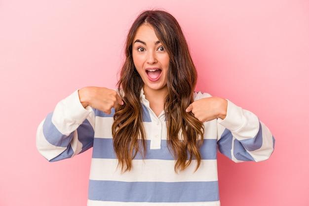 La giovane donna caucasica isolata su fondo rosa ha sorpreso indicando con il dito, sorridendo ampiamente.