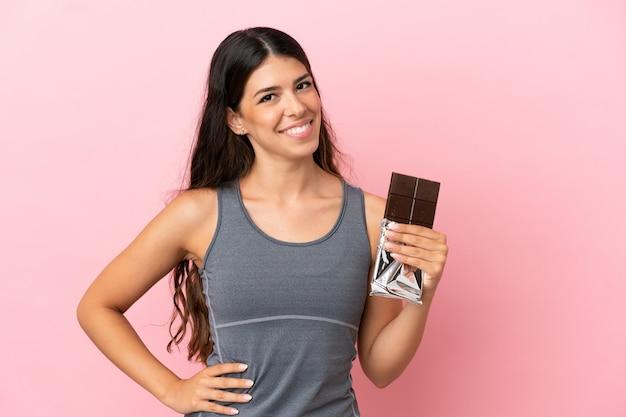 Giovane donna caucasica isolata su sfondo rosa prendendo una tavoletta di cioccolato e felice