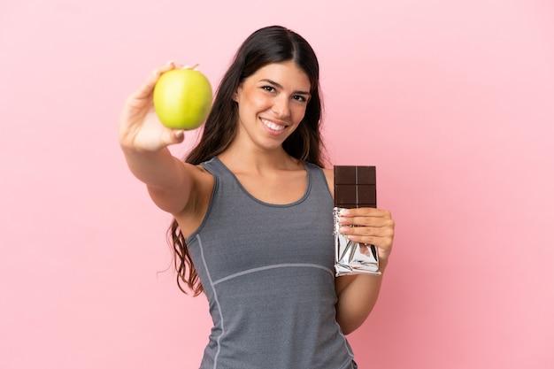Giovane donna caucasica isolata su sfondo rosa che prende una tavoletta di cioccolato in una mano e una mela nell'altra