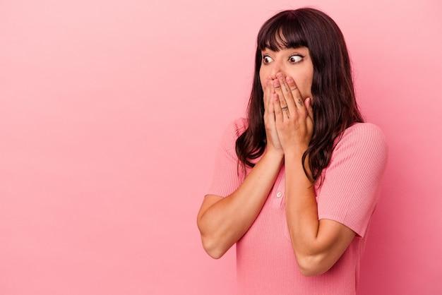 Giovane donna caucasica isolata su sfondo rosa premurosa in cerca di uno spazio copia che copre la bocca con la mano.