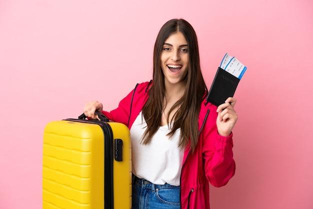 Giovane donna caucasica isolata su sfondo rosa in vacanza con valigia e passaporto