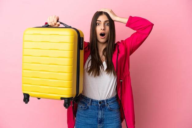 Giovane donna caucasica isolata su sfondo rosa in vacanza con valigia da viaggio e sorpresa