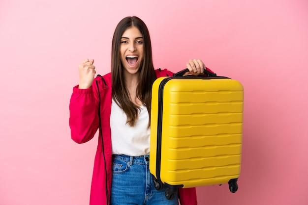 Giovane donna caucasica isolata su sfondo rosa in vacanza con valigia da viaggio