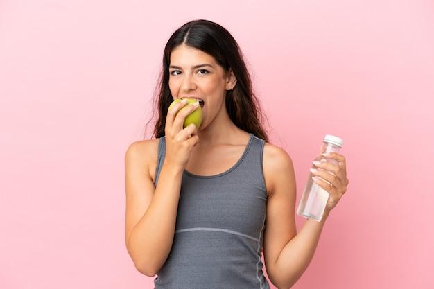 Giovane donna caucasica isolata su sfondo rosa con una bottiglia d'acqua e mangiando una mela