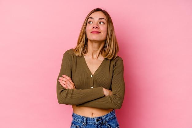 Giovane donna caucasica isolata sul rosa sognando di raggiungere obiettivi e scopi