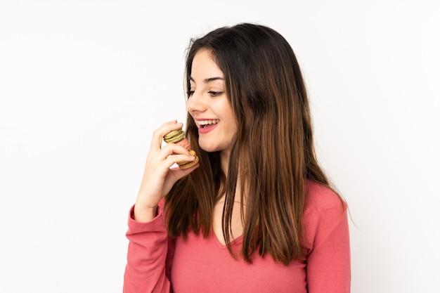 Giovane donna caucasica isolata sul rosa che tiene i macarons francesi variopinti e che lo mangia