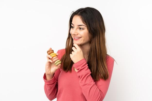 Giovane donna caucasica isolata sul rosa che tiene i macarons francesi variopinti e che pensa un'idea