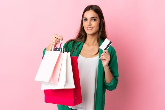 Giovane donna caucasica isolata sui sacchetti della spesa rosa della tenuta e una carta di credito