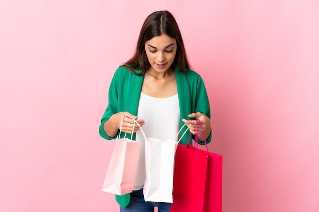 Giovane donna caucasica isolata sui sacchetti della spesa rosa della tenuta e guardando al suo interno