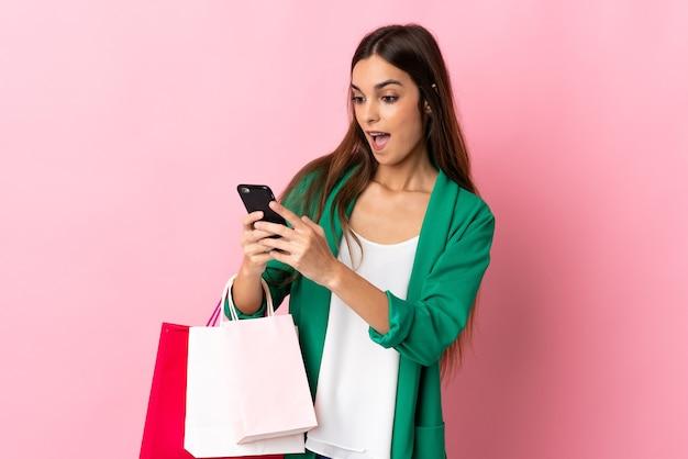 Giovane donna caucasica isolata su rosa che tiene i sacchetti della spesa e scrive un messaggio con il suo telefono cellulare ad un amico