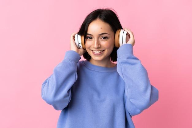 Giovane donna caucasica isolata sulla musica d'ascolto rosa