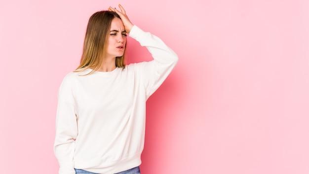 Giovane donna caucasica isolata sullo spazio rosa dimenticando qualcosa, schiaffeggiando la fronte con il palmo e chiudendo gli occhi.