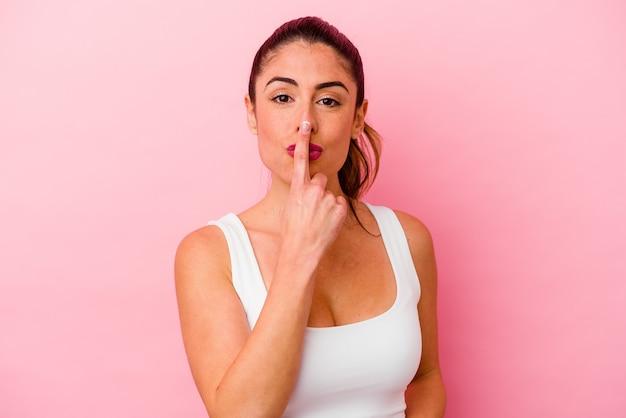 Giovane donna caucasica isolata sul rosa che presta giuramento, mettendo la mano sul petto. Foto Premium