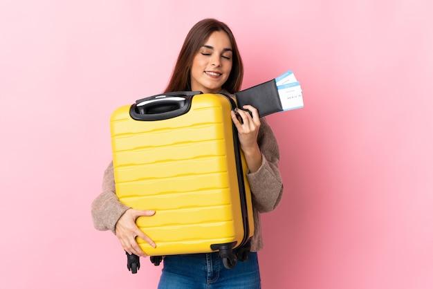 Giovane donna caucasica isolata sul rosa in vacanza con la valigia e il passaporto