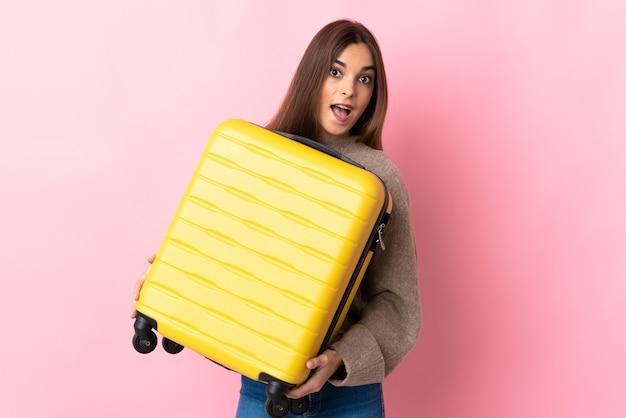 Giovane donna caucasica isolata sul rosa in vacanza con la valigia da viaggio e sorpresa