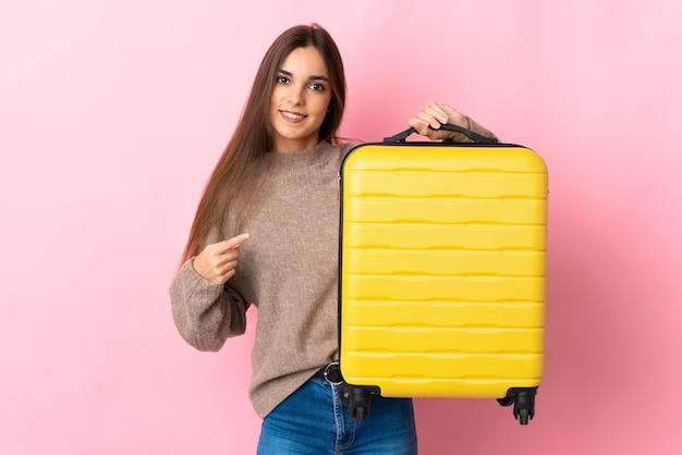 Giovane donna caucasica isolata sul rosa in vacanza con la valigia da viaggio