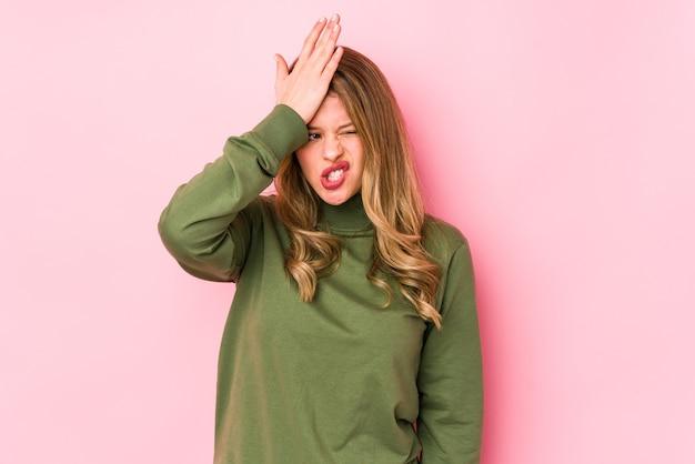 Giovane donna caucasica isolata sul muro rosa dimenticando qualcosa, schiaffi sulla fronte con il palmo e chiudendo gli occhi.