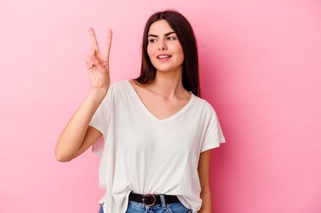 Giovane donna caucasica isolata sulla parete rosa gioiosa e spensierata che mostra un simbolo di pace con le dita.
