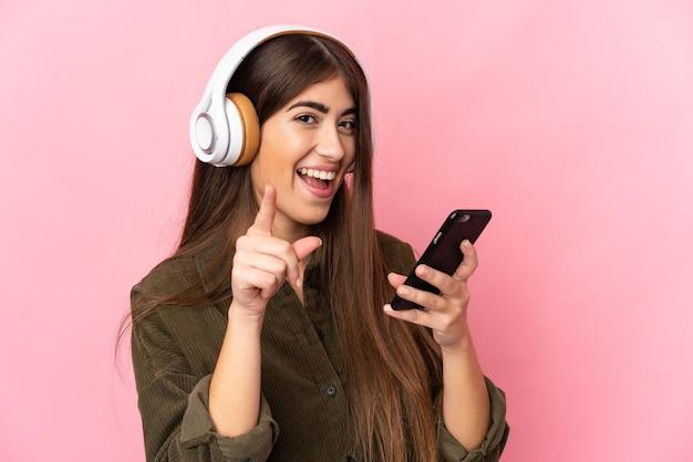 Giovane donna caucasica isolata sulla parete rosa ascoltando musica con un cellulare e cantando