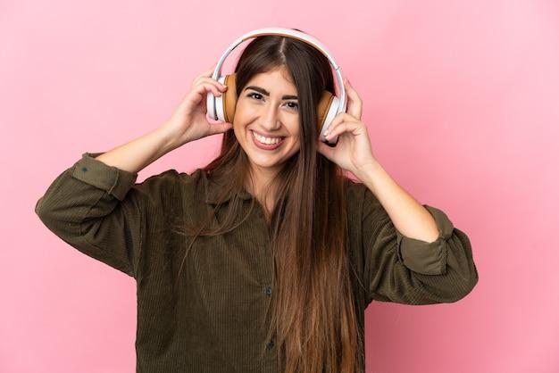 Giovane donna caucasica isolata sulla musica d'ascolto della parete rosa