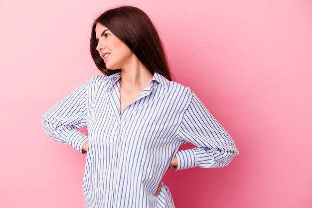 Giovane donna caucasica isolata sulla parete rosa che soffre di mal di schiena.