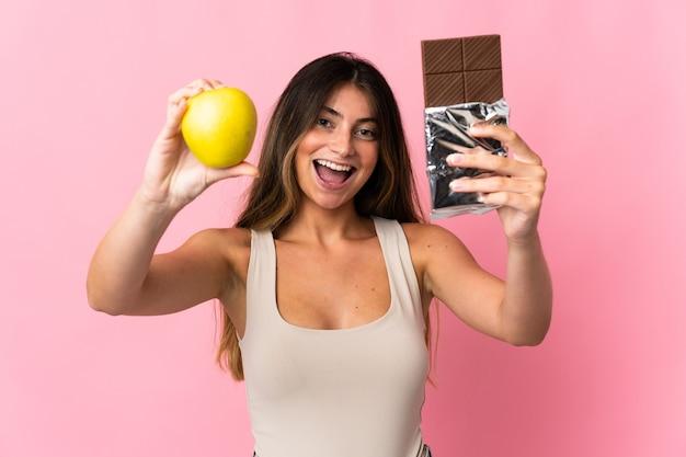 Giovane donna caucasica isolata sul muro rosa prendendo una tavoletta di cioccolato in una mano e una mela nell'altra