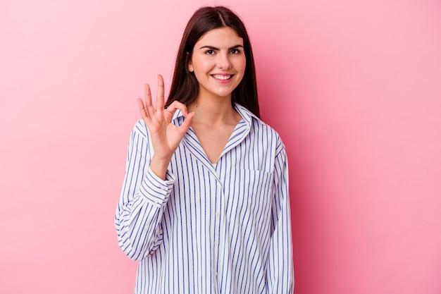 La giovane donna caucasica isolata sulla parete rosa strizza l'occhio e tiene un gesto giusto con la mano.