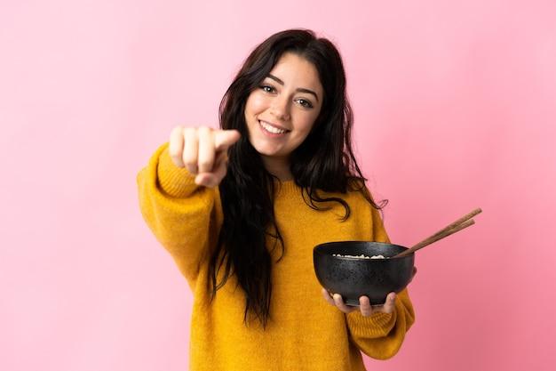 La giovane donna caucasica isolata punta il dito contro di te con un'espressione sicura