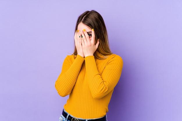 Giovane donna caucasica isolata su sfondo viola sbattere le palpebre verso la telecamera attraverso le dita, imbarazzato che copre il viso.