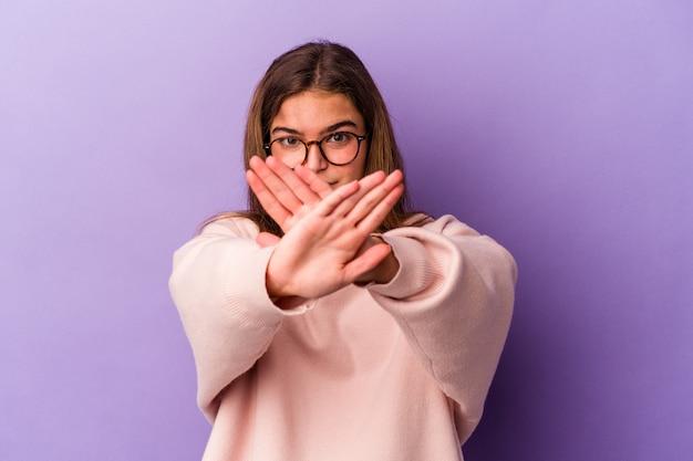 Giovane donna caucasica isolata su sfondo viola che fa un gesto di rifiuto