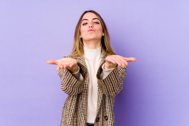 Giovane donna caucasica isolata su sfondo viola piegando le labbra e tenendo le palme per inviare un bacio d'aria.