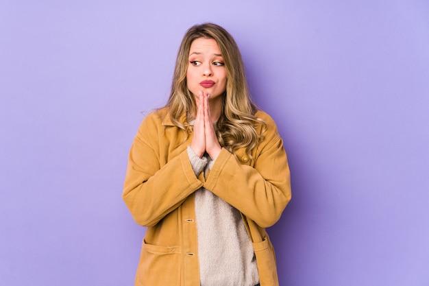 Giovane donna caucasica isolata su sfondo viola pregando, mostrando devozione, persona religiosa in cerca di ispirazione divina.