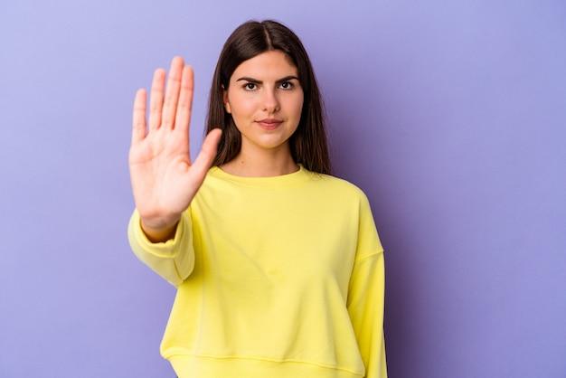 Giovane donna caucasica isolata su sfondo viola in piedi con la mano tesa che mostra il segnale di stop, impedendoti.