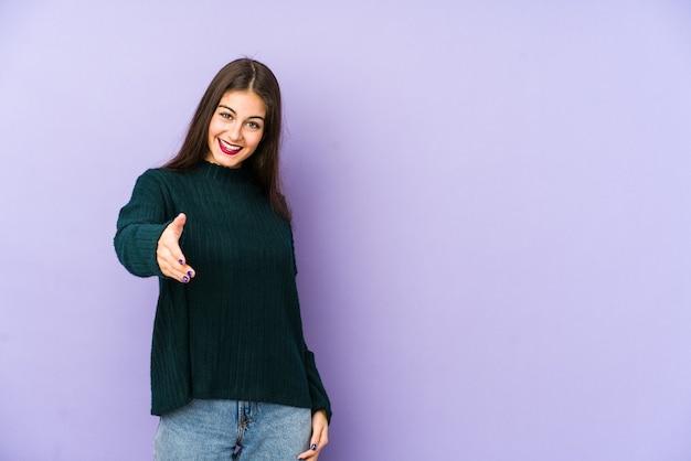 Giovane donna caucasica isolata su sfondo viola che allunga la mano alla macchina fotografica nel gesto di saluto.