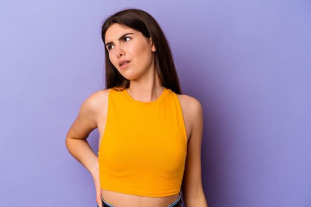 Giovane donna caucasica isolata su sfondo viola che soffre di mal di schiena.