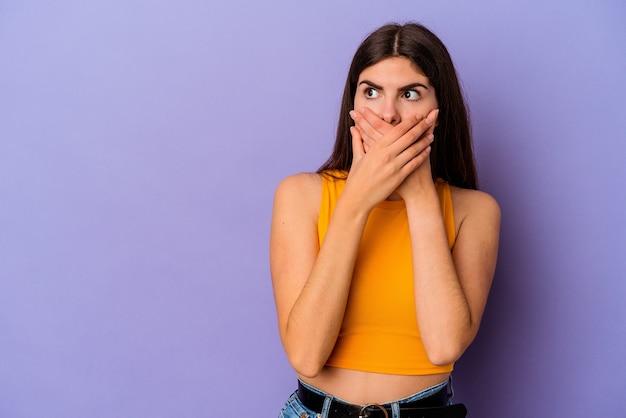 Giovane donna caucasica isolata su sfondo viola premurosa guardando uno spazio copia che copre la bocca con la mano.