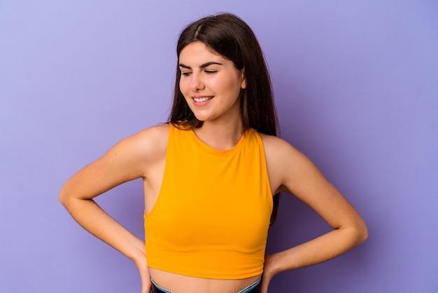 La giovane donna caucasica isolata sul muro viola ride e chiude gli occhi, si sente rilassata e felice.