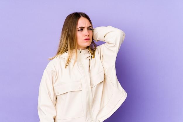 Giovane donna caucasica isolata sulla parete viola stanca e molto assonnata mantenendo la mano sulla testa.