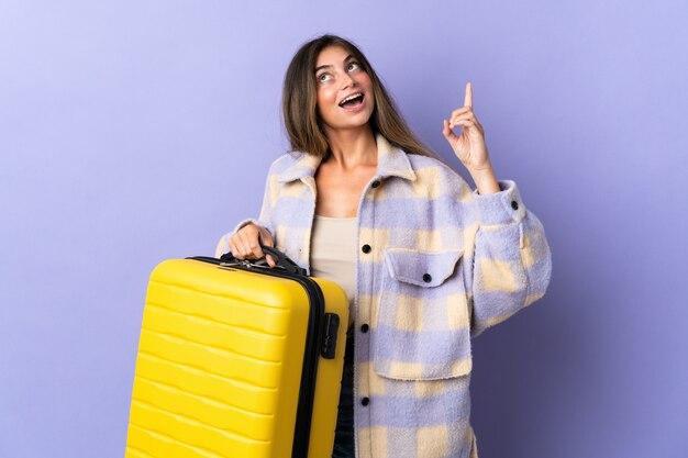 Giovane donna caucasica isolata sulla parete viola in vacanza con la valigia di viaggio e rivolta verso l'alto