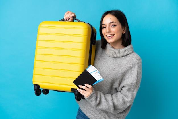 Giovane donna caucasica isolata in vacanza con la valigia e il passaporto