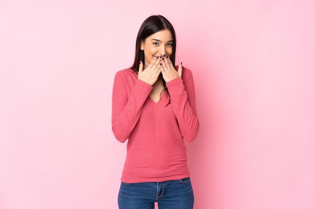 Giovane donna caucasica sul muro isolato felice e sorridente che copre la bocca con le mani