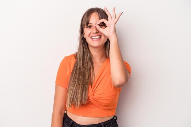 La giovane donna caucasica isolata su fondo bianco ha eccitato mantenendo il gesto giusto sull'occhio.
