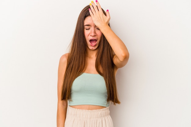 Giovane donna caucasica isolata su sfondo bianco dimenticando qualcosa, schiaffeggiando la fronte con il palmo e chiudendo gli occhi.
