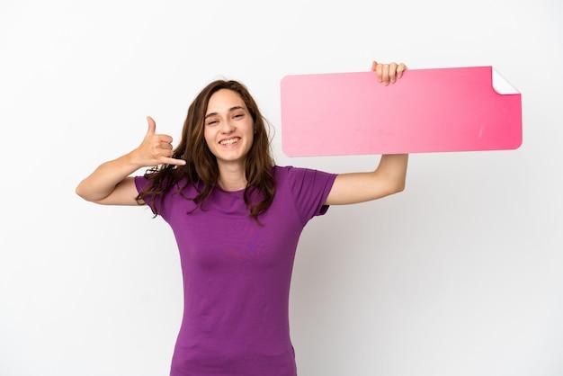 Giovane donna caucasica isolata su fondo bianco che tiene un cartello vuoto e fa il gesto del telefono