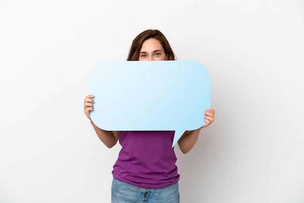 Giovane donna caucasica isolata su sfondo bianco che tiene un fumetto vuoto che si nasconde dietro di esso nascondendosi dietro di esso